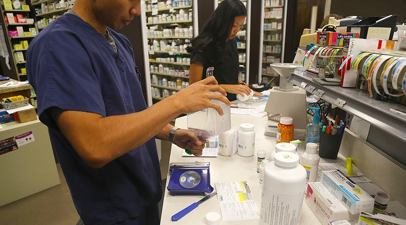 2 techs working on filling prescriptions with pill bottles on counter