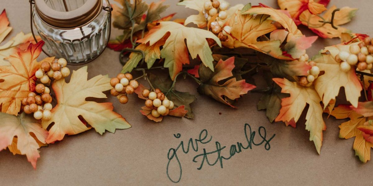 """Text """"Give Thanks"""" surrounded by fall color leaves, berries and candle"""